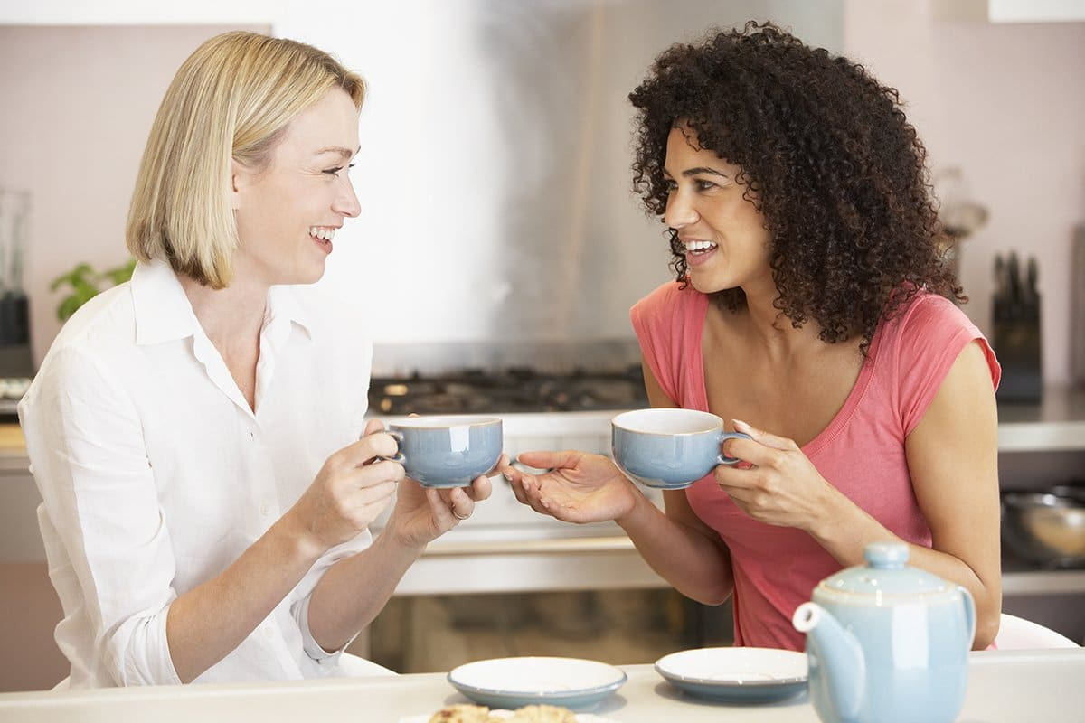 Two girlfriends drinking tea and talking about what helps in menopause