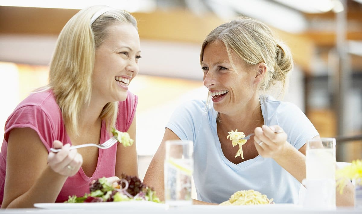 Two women eating lunch and talking about menopause remedies